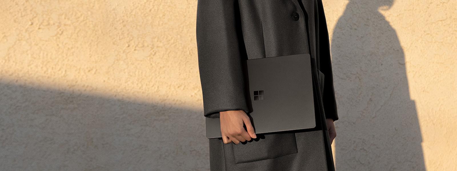 Eine Person in einer schwarzen Jacke hält einen schwarzen Surface Laptop 2 an ihrer Seite