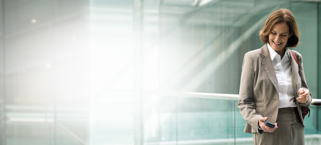 Eine Geschäftsfrau verwendet im Stehen die Exchange Online-Archivierung auf ihrem Smartphone.