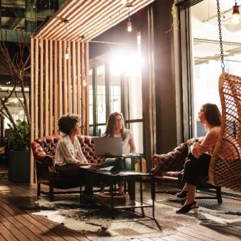 Drei Personen, die im Büro an einem kleinen Tisch sitzen und sich unterhalten, und eine stehende Person, die an einem Laptop arbeitet