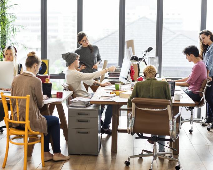 Mehrere Personen an einem Bürotisch bei der Teamarbeit