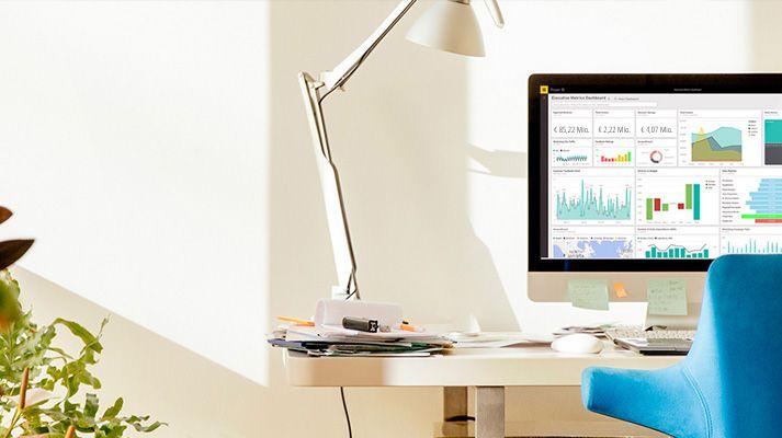 Schreibtisch mit einem blauen Stuhl und einem Computerbildschirm, auf dem Power BI ausgeführt wird