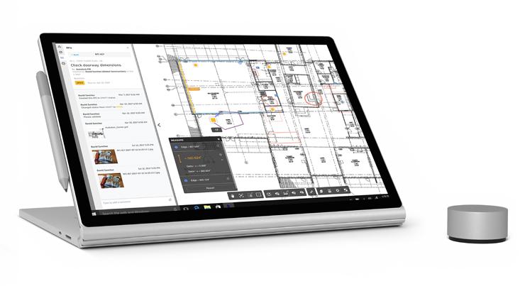 Surface Book 2 im Tablet-Modus, wobei die Tastatur zum Ständer gefaltet ist, mit Pen- und Dial-Zubehör.