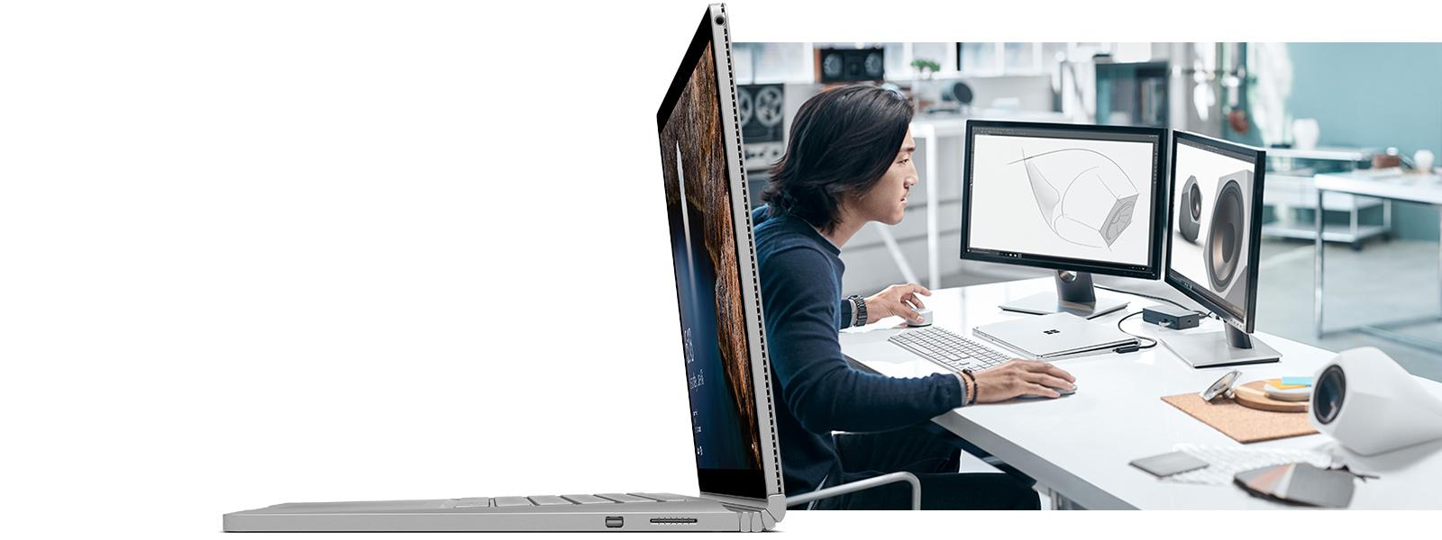 Ein Mann, der an einem Schreibtisch sitzt und auf einem Surface Book mit angeschlossener Tastatur, Maus und zwei externen Bildschirmen arbeitet