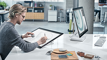 Ein Mann zeichnet auf Surface Studio-Bildschirm und nutzt Dial in einer modernen Büroumgebung, ihm gegenüber ein weiteres Surface Studio