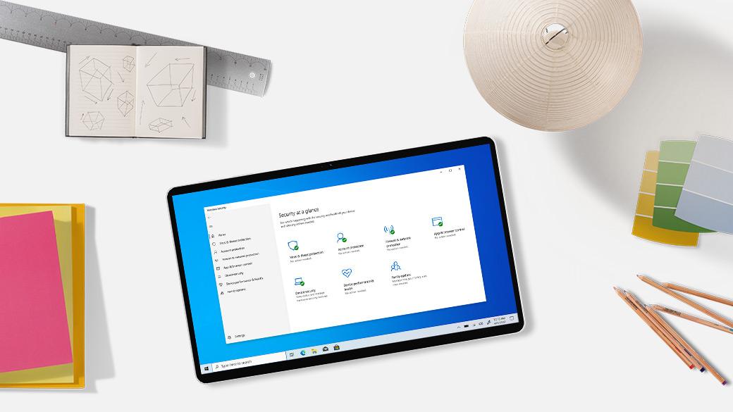 Tablet auf einem Schreibtisch mit Lampe, Stiften, Lineal, Zeichnung und Ordnern.