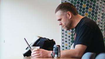 Ein Mann sitzt mit seinem Windows10-PC an einem Tisch und arbeitet