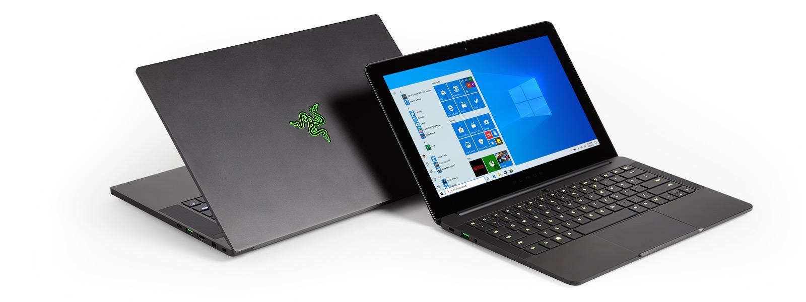 Zwei Razer-Computer, die Rücken an Rücken stehen, wobei auf dem einen der Windows 10-Startbildschirm und App-Kacheln wie Xbox und Netflix zu sehen sind