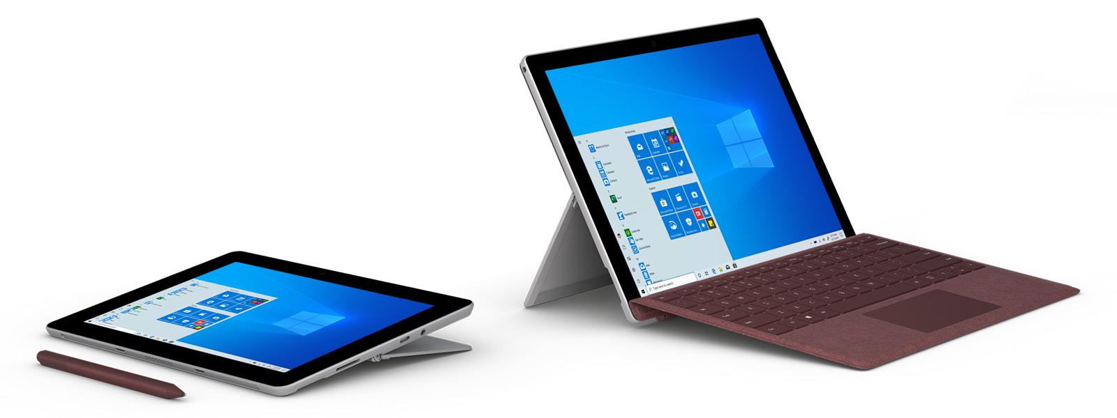 Zwei Surface Go-Computer stehen nebeneinander.  Einer davon liegt flach und ein Stift liegt davor, darauf ist der Windows 10 Startbildschirm zu sehen.  An den anderen Laptop ist eine Tastatur angeschlossen und der Windows 10-Startbildschirm ist zu sehen.