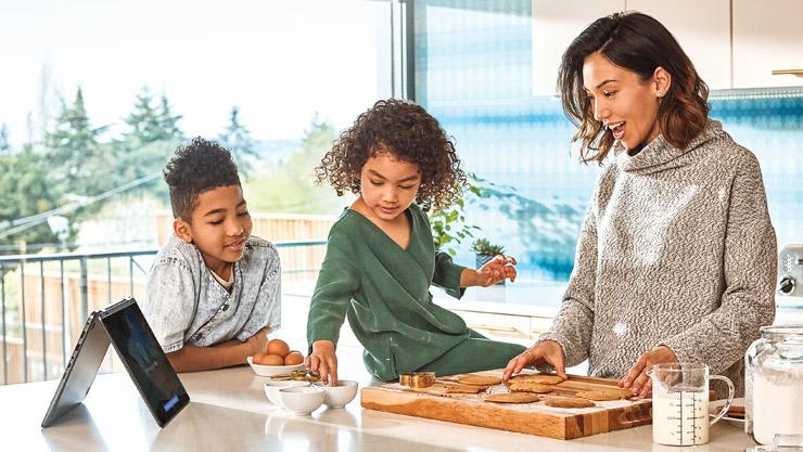 Mutter und ihre Kinder backen Kekse, während sie mit ihrem Windows 10-Computer interagieren
