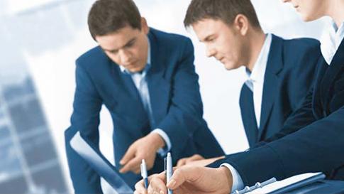 Zwei Männer sitzen an einem Schreibtisch und deuten auf einen Laptopbildschirm