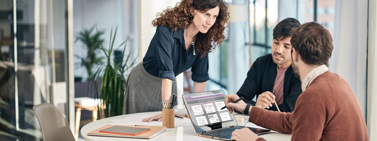 Zwei Männer sitzen an einem Tisch vor einem laptop und eine Frau steht daneben