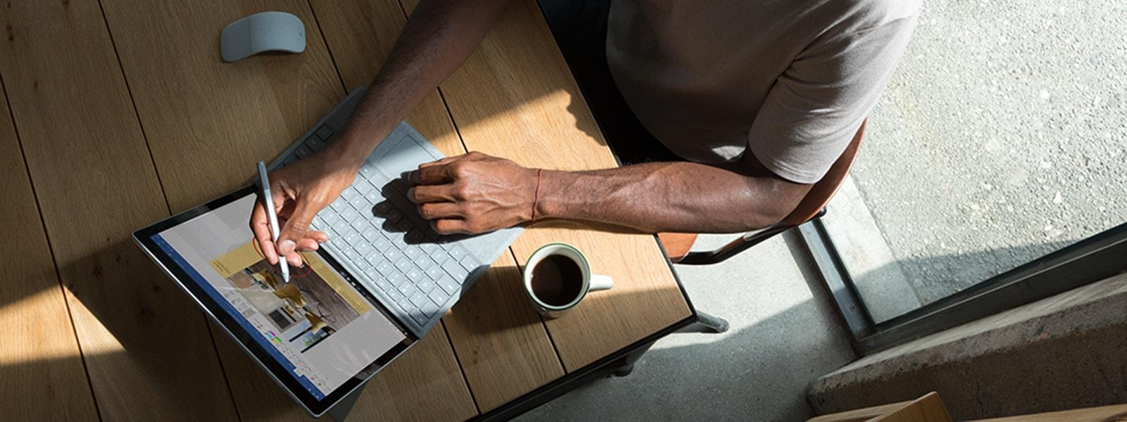Mann mit Surface-Stift schreibt in einer Café-Umgebung auf einem SurfacePro.