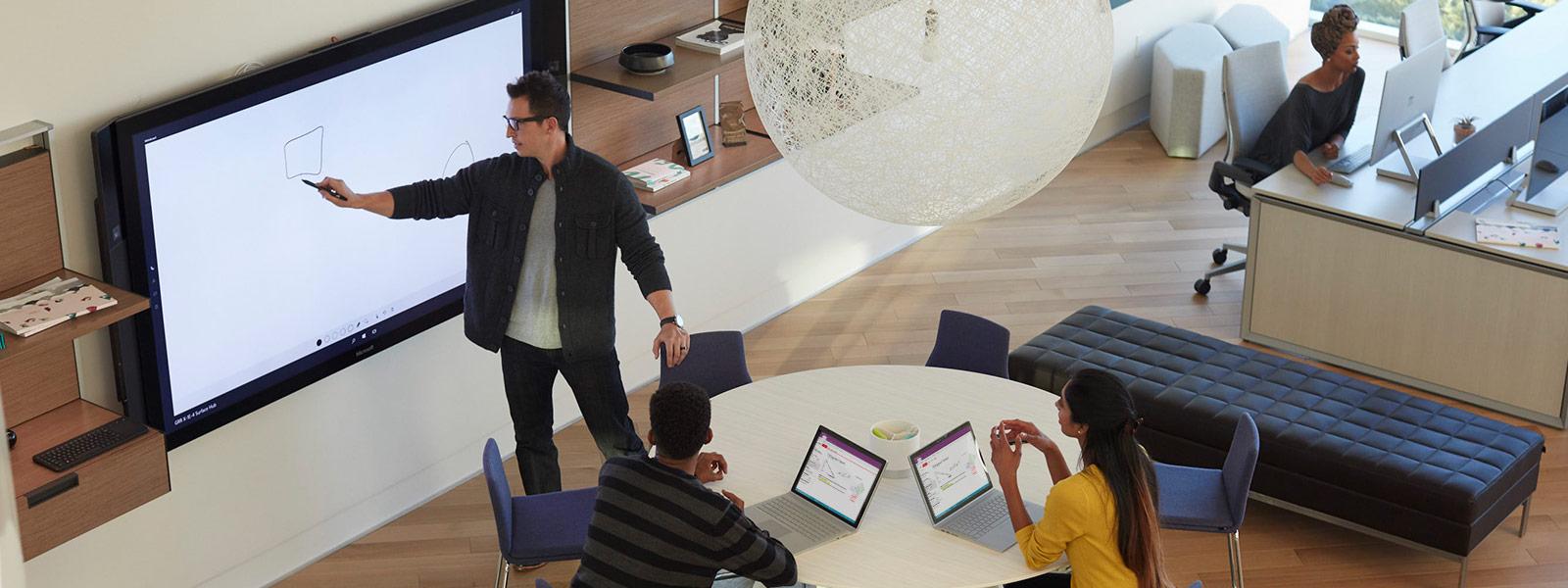 Lehrer hält Präsentation auf Surface Hub, während Schüler am Tisch auf Surface Books tippen.