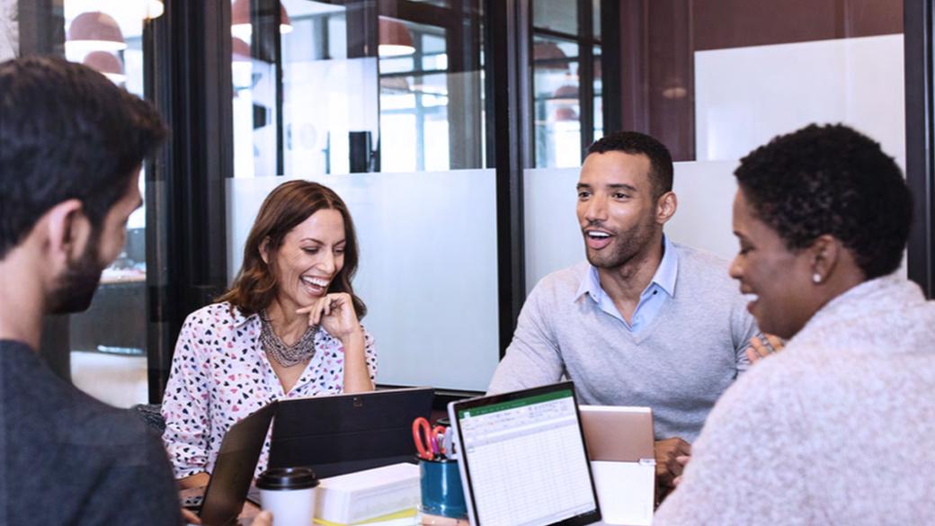 Vier Mitarbeiter sitzen an Konferenztisch mit Surface Pro4 und anderen Surface-Geräten.