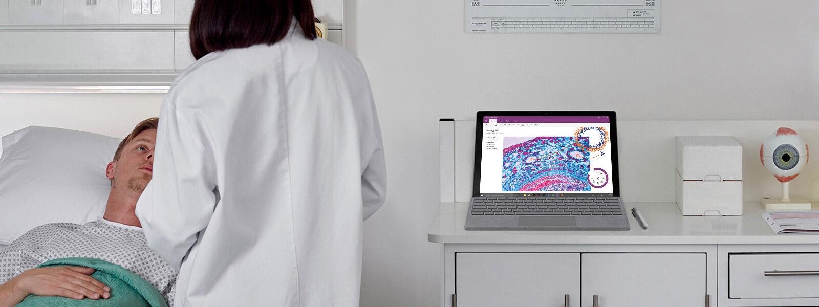 Arzt in Patientengespräch an Krankenbett mit Surface Book auf Tisch im Hintergrund.