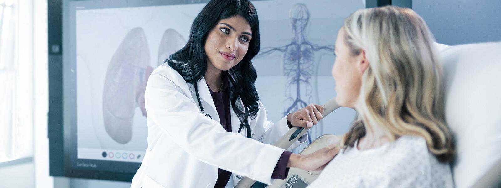 Arzt misst Vitaldaten an Krankenbett mit Surface Hub im Hintergrund.