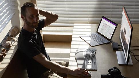 Ein Mann sitzt an seinem Schreibtisch mit einem Surface Laptop und einem Surface Studio.