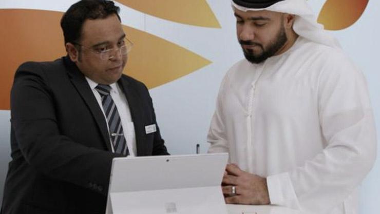 Mashreq-Mitarbeiter und Kunde teilen auf Surface Pro Informationen miteinander.