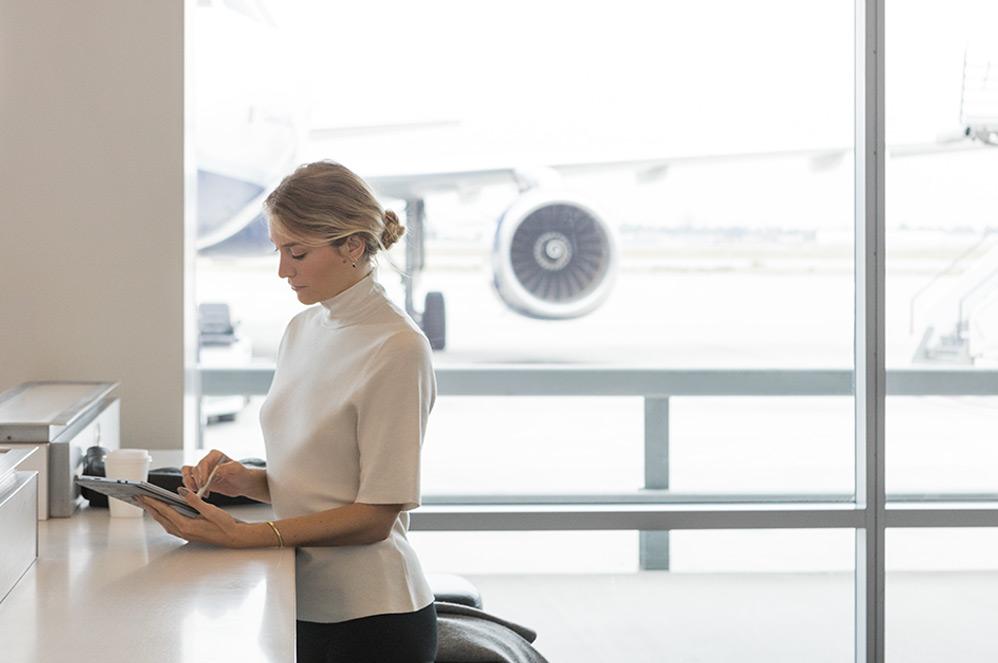 Eine Frau am Flughafen arbeitet an ihrem Surface Pro (5.Gen) mit 4G LTE im Tablet-Modus mit Surface Pen