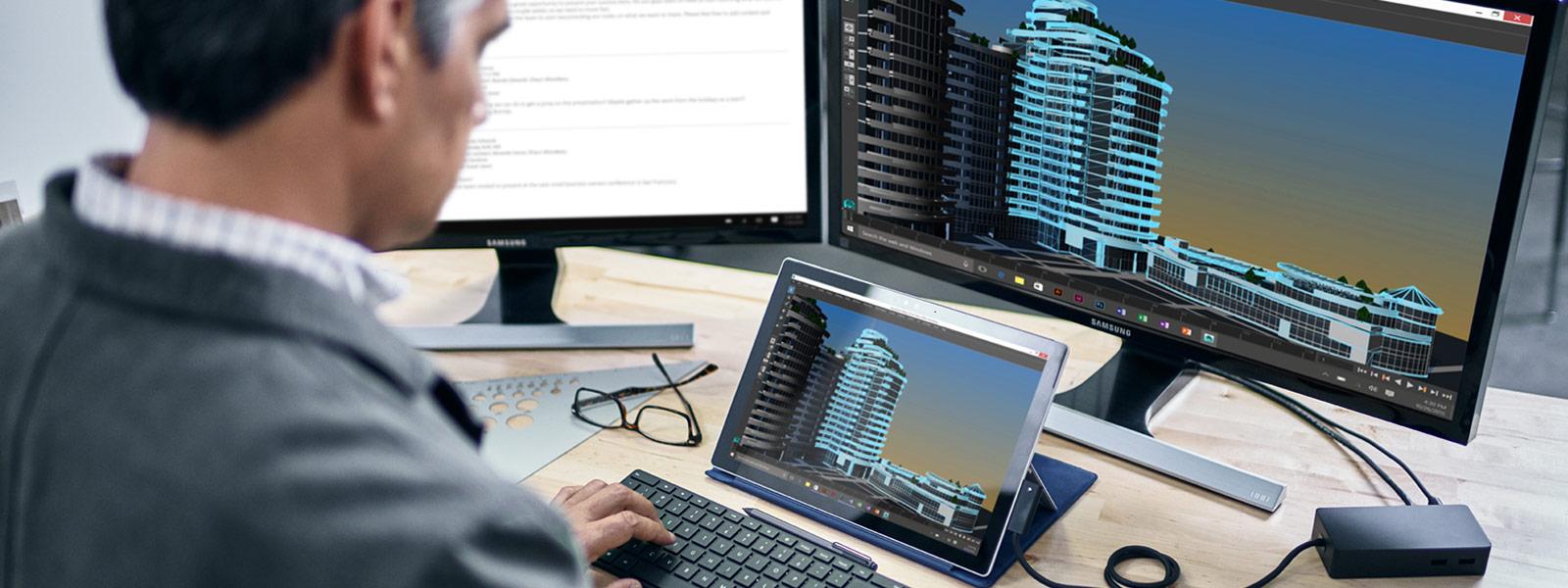 Mann tippt auf Surface Pro 4 mit Surface Dock und Desktopcomputer auf Schreibtisch.