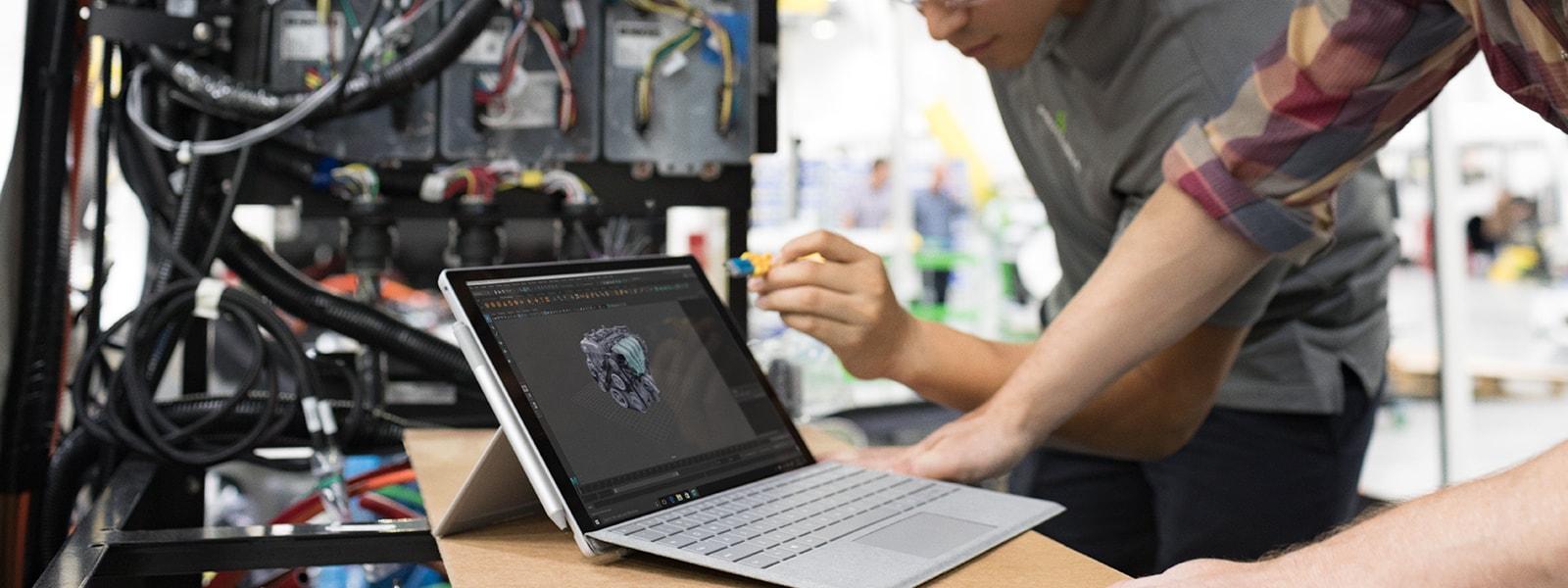 Zwei Männer verwenden AutoCad auf einem Surface Pro auf dem Tisch.
