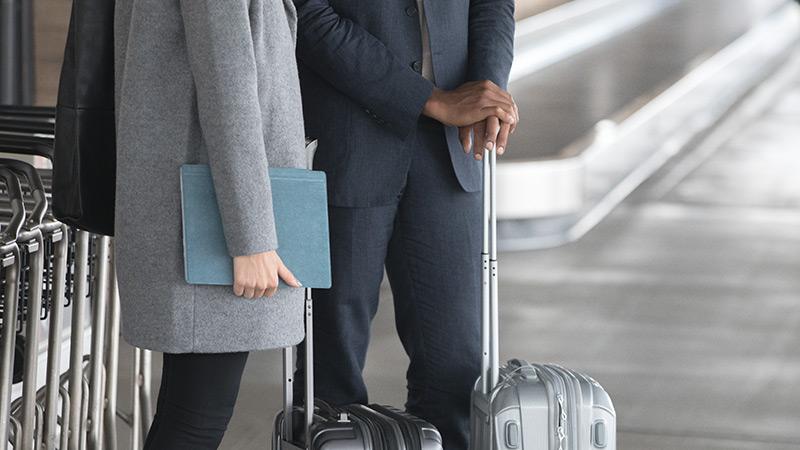 Eine Frau steht am Flughafen neben einem Mann und hält ein kobaltfarbenes Surface Pro in den Händen.