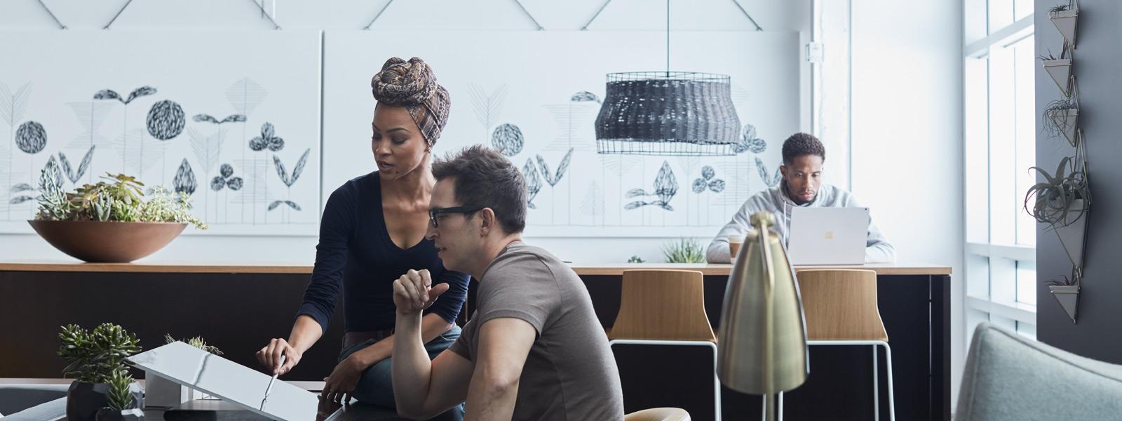 Mann und Frau, in einer Steelcase-Umgebung auf ein Surface Studio blickend.