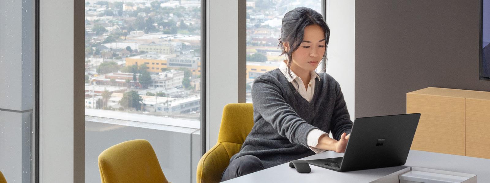 Eine Frau arbeitet an ihrem Schreibtisch mit ihrem SurfaceLaptop2 in Mattschwarz.