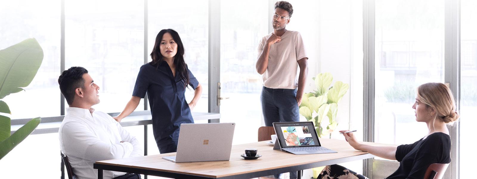 Ein Team versammelt sich um einen Konferenztisch mit Surface-Geräten.
