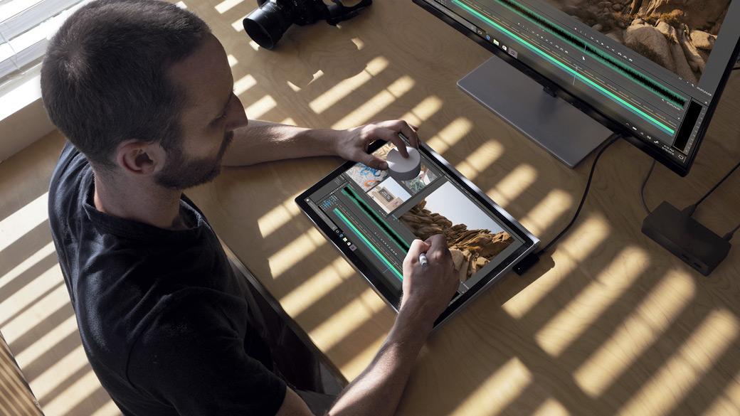 Ein Mann bearbeitet auf einem Surface-Gerät mithilfe des Surface Pen und Surface Dial ein Foto.