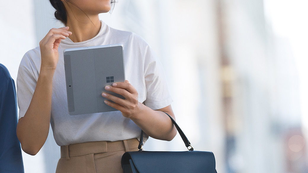 Eine Frau arbeitet im Gehen mit einem Surface-Gerät.