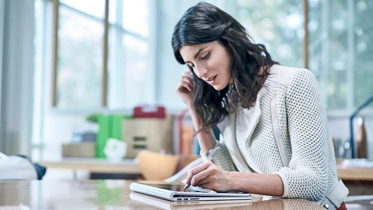 Frau verwendet Stift auf Surface Book im Clipboard-Modus.