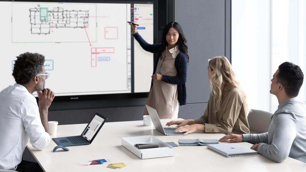 Eine Frau in einem Vorstandszimmer präsentiert ihren Kollegen etwas auf Surface Hub.