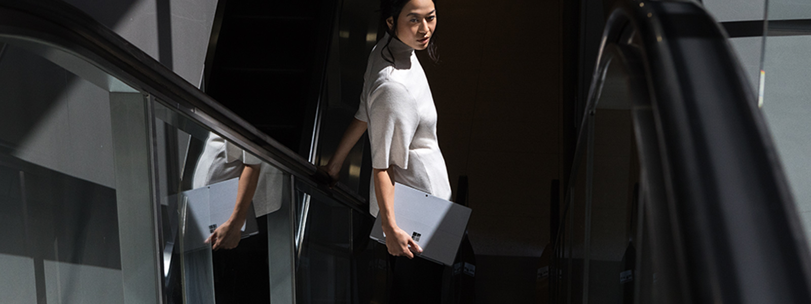 Frau hält Surface Pro, während sie auf einer Rolltreppe nach unten fährt.