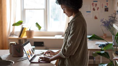 Kenesha, Inhaberin eines Kleinunternehmens, tippt auf einem weinroten Surface Laptop.