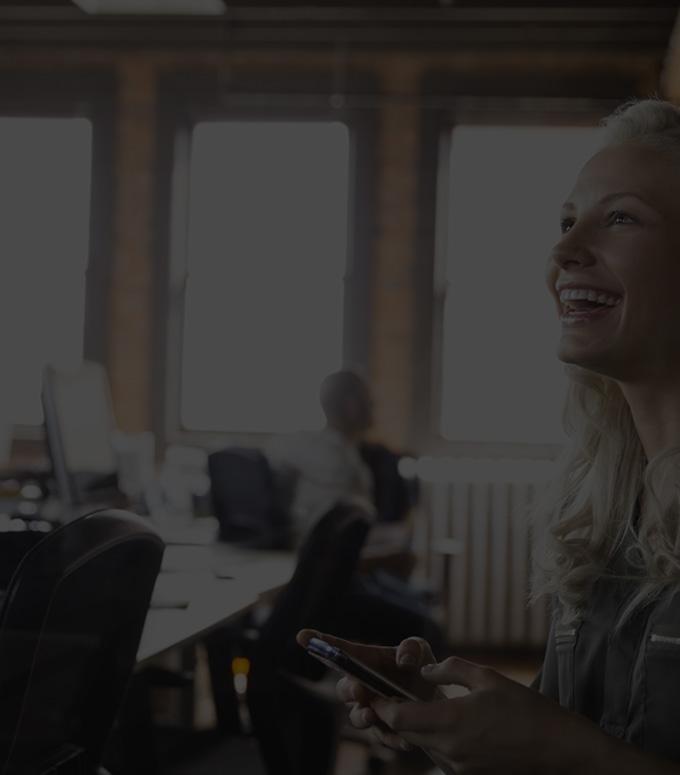 Eine Frau in einem Büro führt Office 365 Business Essentials auf einem Smartphone aus.