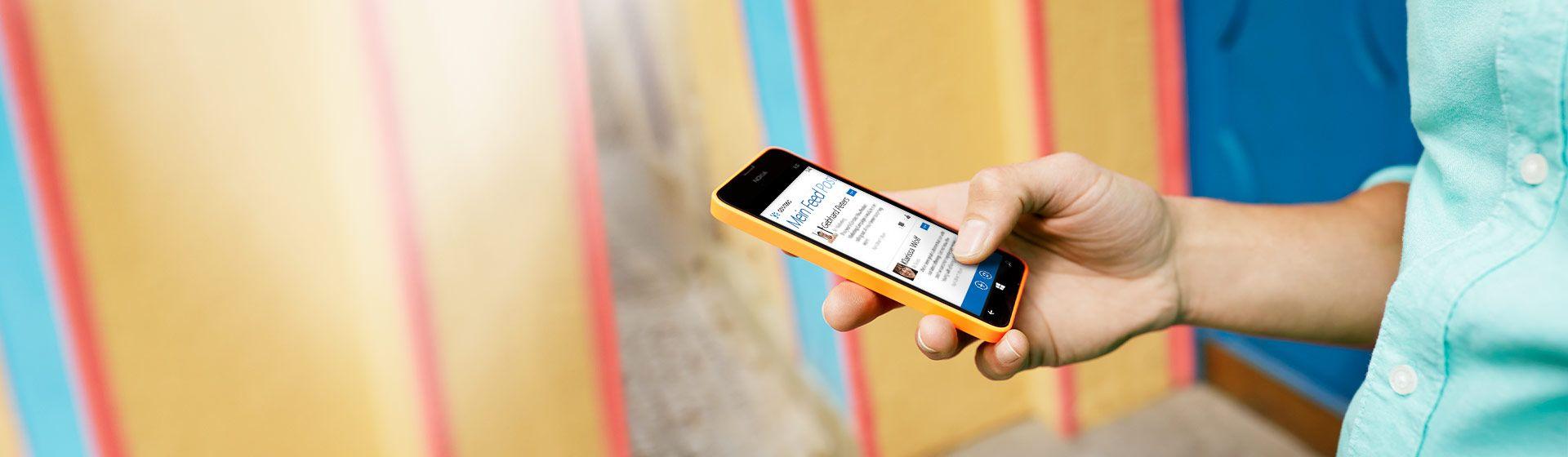 Ein Mann mit einem Windows Phone in der Hand, auf dem der Feed in der mobilen Yammer-App angezeigt wird