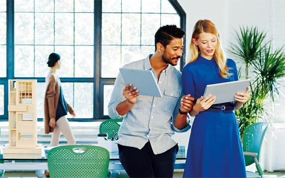 Ein Mann und eine Frau arbeiten im Büro an ihren Tablets.