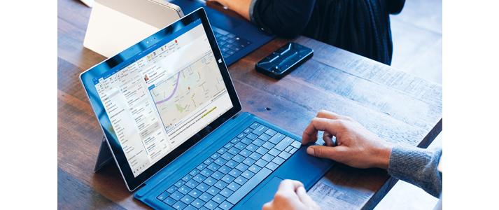 Ein Mann, der an einem Microsoft Surface Book in Outlook arbeitet