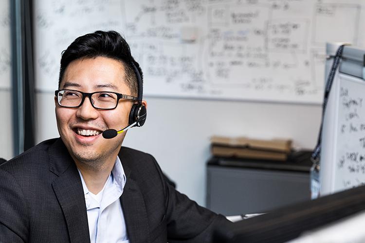 Eine Person mit Brille, die an einem Schreibtisch sitzt und ein Headset trägt