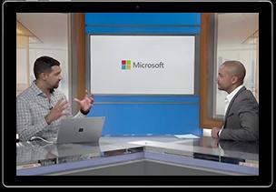 """Videostandbild des Webcasts """"Microsoft 365 Enterprise: Produktive Mitarbeiter"""". Zwei Personen sitzen an einem Tisch und unterhalten sich."""