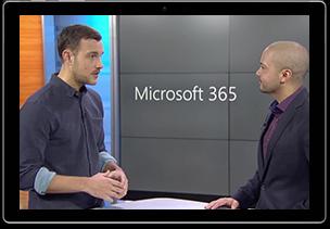 Zwei Personen stehen zusammen und unterhalten sich. Im Hintergrund wird der Schriftzug Microsoft 365 angezeigt.