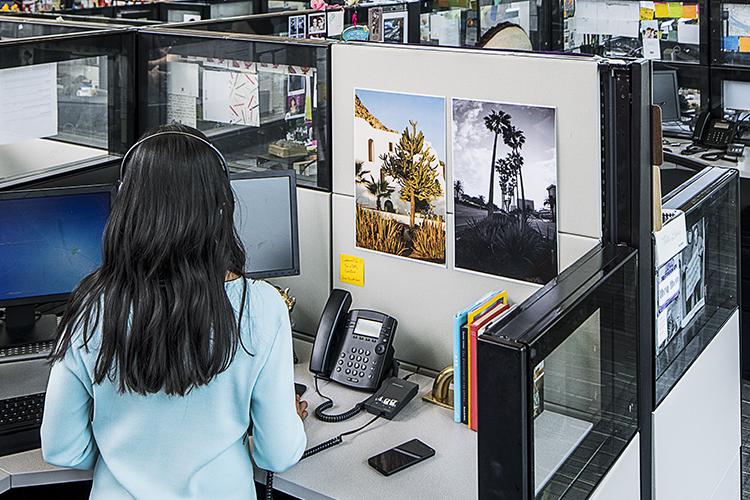 Eine Frau mit Headset, die an ihrem Arbeitsplatz telefoniert