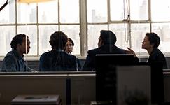 Ein Blick in einen Konferenzraum, in dem sich Mitarbeiter unterhalten