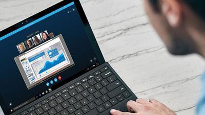 Eine Person, die an einem Laptop arbeitet, auf dem ein Konferenzanruf angezeigt wird