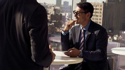 Eine Person an einem runden Bürotisch, die ein Mobilgerät in der Hand hält