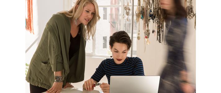 Zwei Frauen schauen auf einen Laptop
