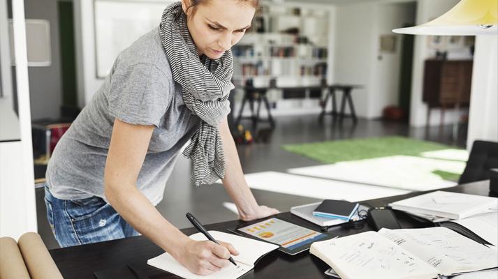 Nahaufnahme einer Frau, die sich über einen Schreibtisch mit Smartphone und Tablet beugt und sich Notizen macht