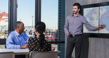 Ein Mann steht vor einem Präsentationsbildschirm und zeigt auf einen Punkt, während zwei Person an einem Tisch seinem Vortrag folgen.