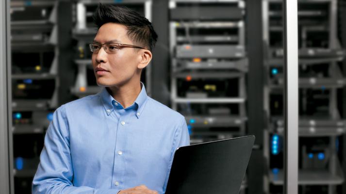 Ein Mann steht mit einem geöffneten Laptop in der Hand in einem Rechenzentrum und blickt zur Seite.